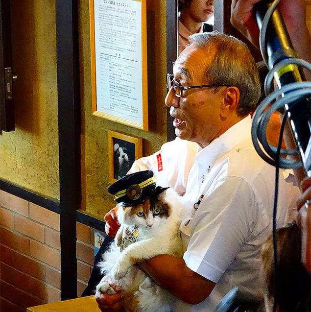 Nitama é fotografada no colo de Mitsunobu Kojima, presidente da Wakayama Electric Railway, durante a cerimônia de posse (Reprodução/Instagram/masami_furu)