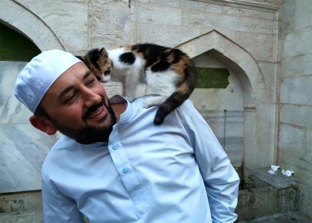O imã Mustafa Efe brinca com uma gatinha na mesquita, em Istambul (Reprodução/Facebook/Mustafa Efe )