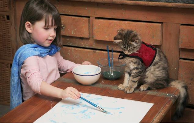 A gatinha Thula presta atenção enquanto Iris pinta uma de suas telas (Reprodução/Facebook/Iris Grace Painting)