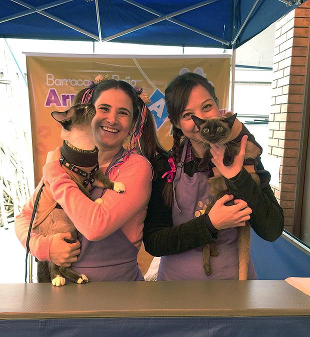 Juliana Bussab (à esq.) e Susan Yamamoto, fundadoras da AUG, com os gatinhos da barraca do beijo, durante o 1º Arraial do AUG, em julho de 2015 (Divulgação/AUG)